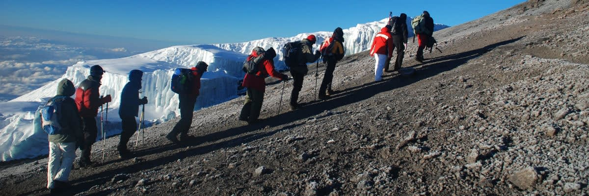 A line of trekkers trudging towards Uhuru Peak past Rebmann Glacier