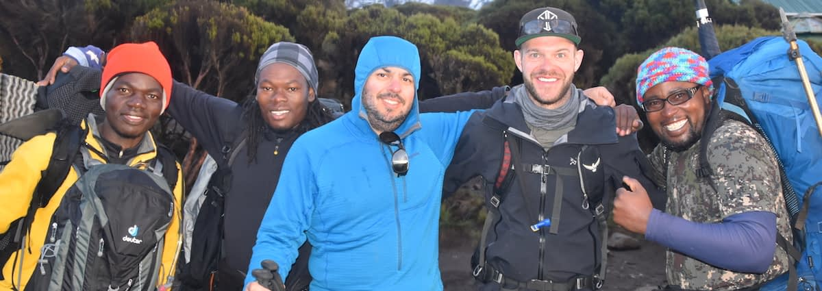 Guides and trekkers on the northern side of Kilimanjaro, arms round each other, smiling at the camera. It looks cold.