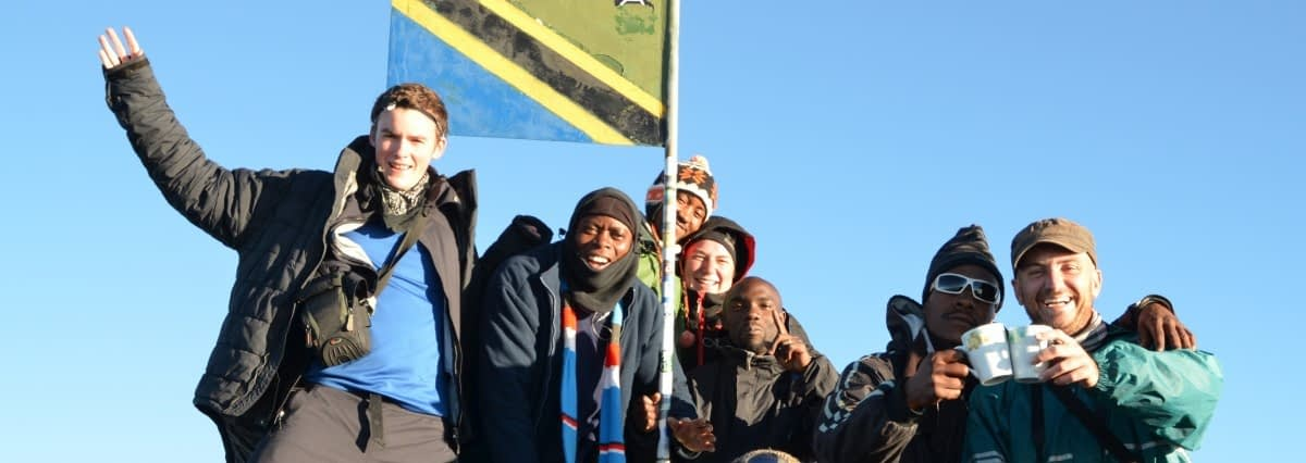 A group of trekkers celebrating at the summit of Mount Meru in front of the Tanzanian flag