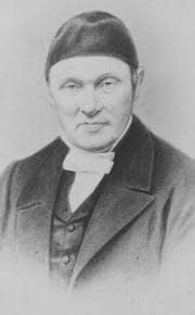 Faded black-and-white photograph of Johann Ludwig Krapf, dressed in cap and wearing a white bow tie