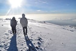 Two men trudging through the snow at the top of The Roof of Africa