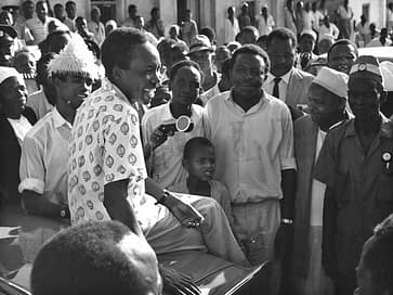 A smiling Julius Nyerere relaxing on the bonnet of a car surrounded by a crowd