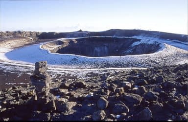 The Reusch Crater and the Ash Pit with a small cairn in the foreground and a light dusting of snow