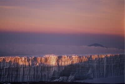 Kilimanjaro's Southern Icefield as seen from Uhuru Peak at dawn, with a beautiful pinky-orange sky and Mount Meru breaking through the clouds in the distance