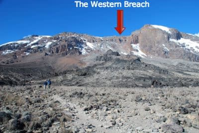 Kibo's Western Breach as seen from below on the Shira Plateau, with two small figures of trekkers in the middle distance.