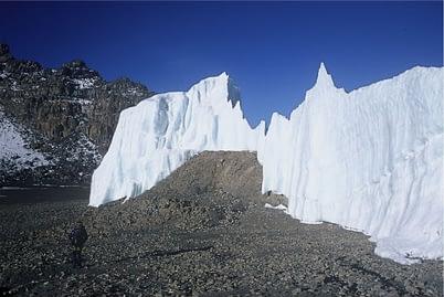 Guide walking on the Kibo crater floor past Furtwangler Glacier