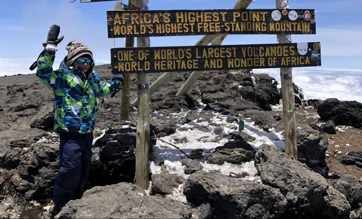 Coaltan Tanner, the youngest person to reach the summit, celebrating at the top of kilimanjaro