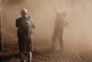 Two trekkers at the start of Kilimanjaro's Rongai Route walking through the dust