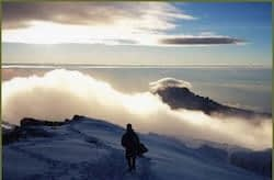 Solo trekker walks through the snow on Kilimanjaro's crater rim