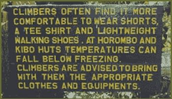 Sign with yellow lettering on a wooden board advising climbers that shorts and T-shirt are OK at lower altitudes, but temperatures at Horombo Huts can dip below freezing