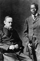 An elderly, bearded Johannes Rebmann, seated on the left, with a Tanzanian man standing on the right