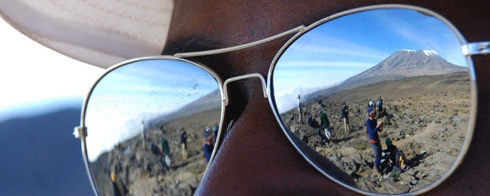 Kilimanjaro's main summit, Kibo, reflected in the sunglasses of a guide