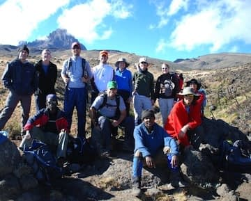 Having booked their trek on Kilimanjaro, this group of trekkers stop for photos in front of Mawenzi