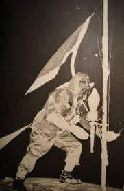 A soldier, fighting against a high wind, places a torch on the summit of Kilimanjaro