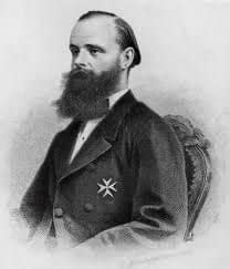 Baron Carl Claus von der Decken, seated and with a large black beard, sitting with a German Empire medal pinned to his jacket