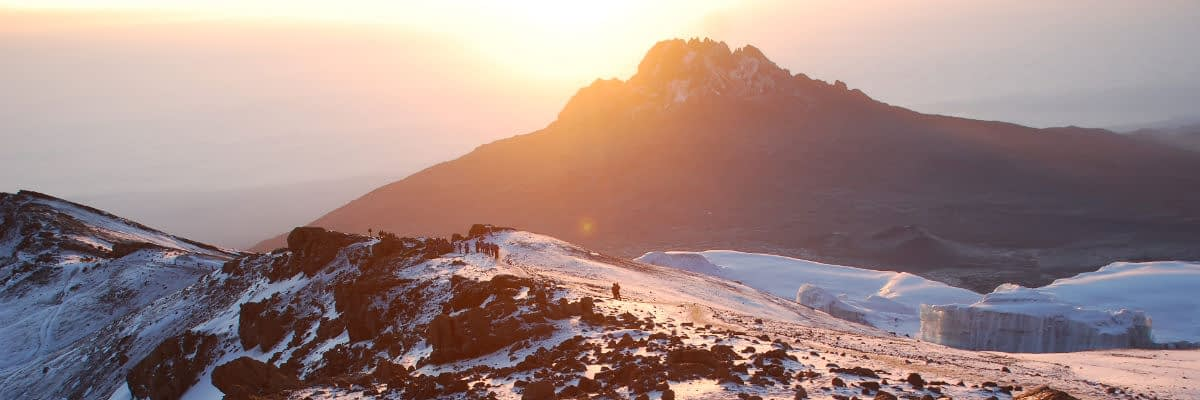 Trekkers on the Crater rim with glaciers and Mawenzi in the background