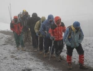 A line of trekkers and guides struggling up Kilimanjaro's Kibo summit in the snow