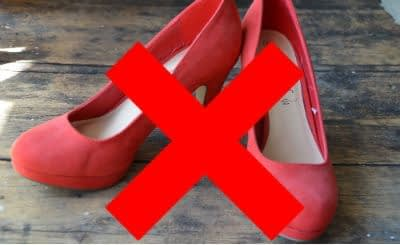 Pair of red suede high heels on wooden floorboards with a large red cross through to show that they're not suitable for Kilimanjaro